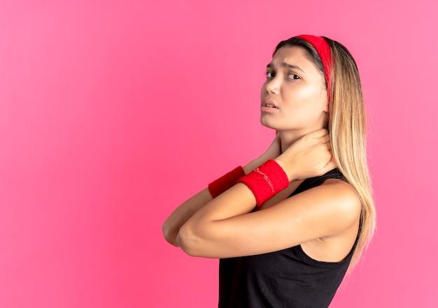 Junges fitness-mädchen in schwarzer sportbekleidung und rotem stirnband, das ihren hals berührt, der unwohl fühlt schmerz über rosa