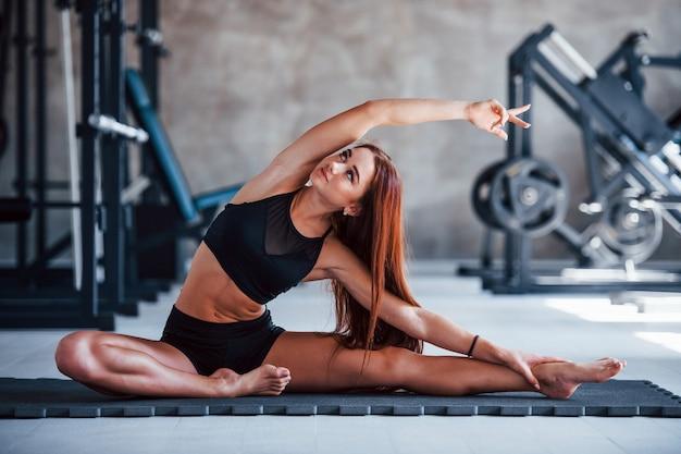 Junges fitness-mädchen in schwarzer sportlicher kleidung, das yoga-übungen im fitnessstudio macht.