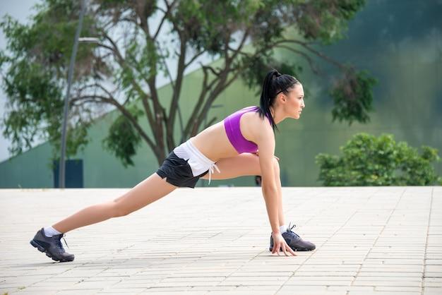 Junges fitness-mädchen macht dehnübungen im freien
