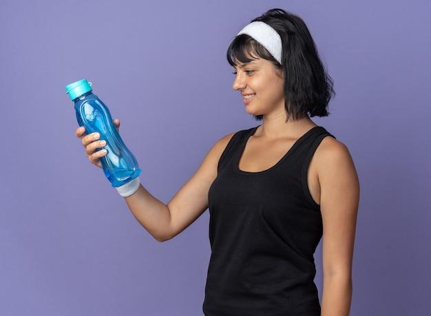 Junges fitness-mädchen mit stirnband, das eine wasserflasche hält und es mit einem lächeln auf dem gesicht betrachtet, das über blauem hintergrund steht