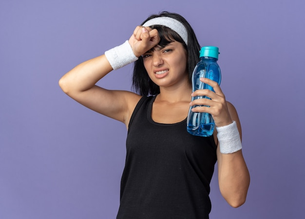 Junges fitness-mädchen mit stirnband, das eine wasserflasche hält und müde und überarbeitet auf blauem hintergrund steht