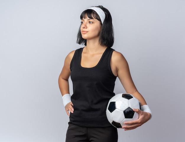 Junges fitness-mädchen mit stirnband, das fußball hält und mit ernstem gesichtsball über weiß steht