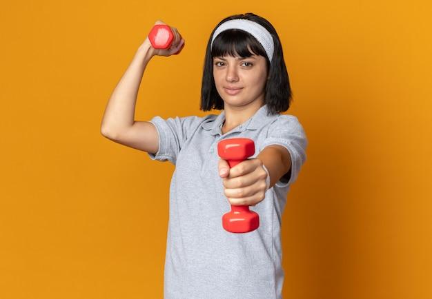 Junges fitness-mädchen mit stirnband, das hanteln hält und übungen macht, die selbstbewusst auf orangefarbenem hintergrund stehen