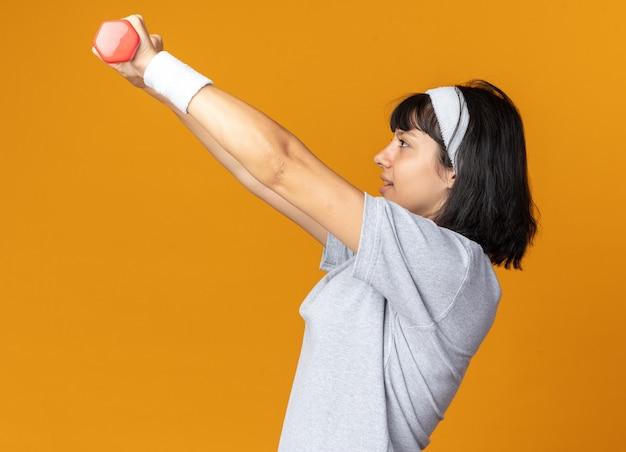 Junges fitness-mädchen mit stirnband, das hanteln hält und übungen macht, die selbstbewusst über orange aussehen