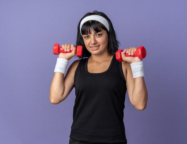 Junges fitness-mädchen mit stirnband, das hanteln hält und übungen macht, die verwirrt aussehen