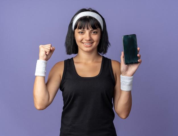 Junges fitness-mädchen mit stirnband, das smartphone mit geballter faust glücklich und aufgeregt in die kamera schaut