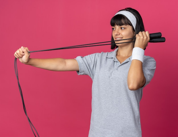 Junges fitness-mädchen mit stirnband, das springseil hält und mit einem lächeln auf einem glücklichen gesicht auf rosafarbenem hintergrund beiseite schaut