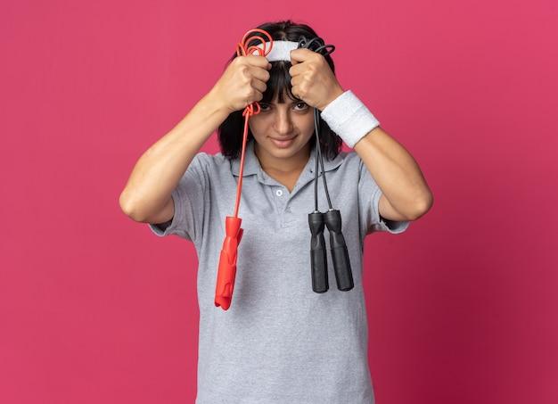 Junges fitness-mädchen mit stirnband, das springseile hält, die verwirrt aussieht und versucht, eine wahl zu treffen?