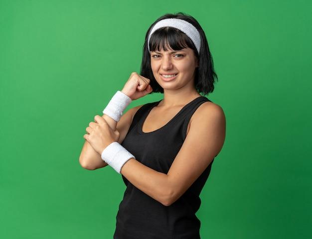 Junges fitness-mädchen mit stirnband, das unwohl aussieht und ihren ellbogen berührt, fühlt sich unwohl