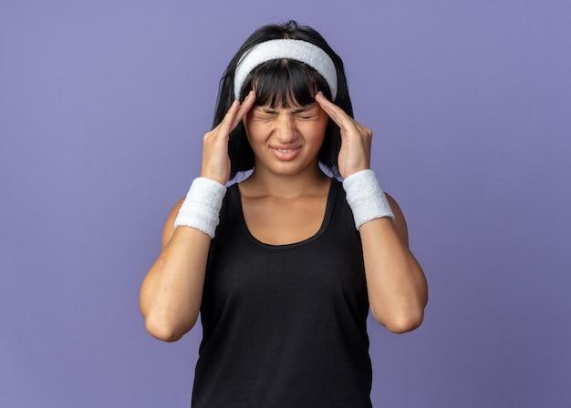 Junges fitness-mädchen mit stirnband, das unwohl aussieht und ihren kopf berührt, der unter kopfschmerzen leidet, die auf blauem hintergrund stehen