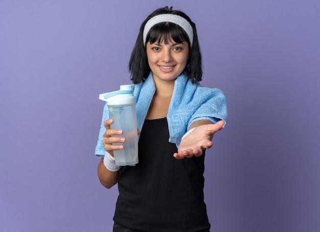 Junges fitness-mädchen mit stirnband mit handtuch um den hals, das eine wasserflasche hält und die kamera ansieht, lächelt freundlich und macht hierher geste mit der hand, die über blauem hintergrund steht