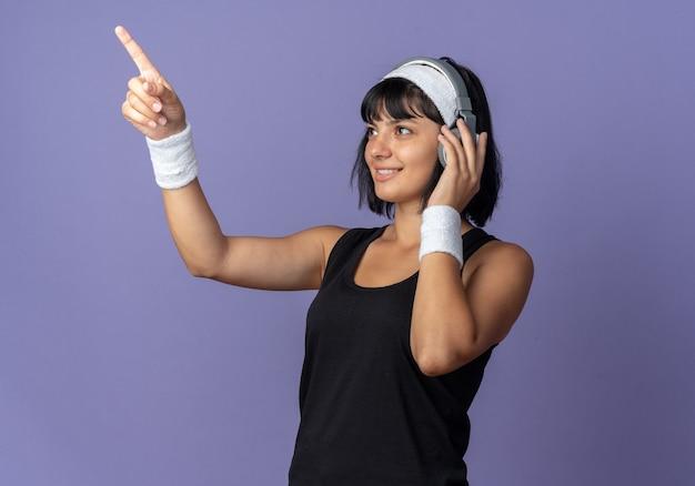 Junges fitness-mädchen mit stirnband mit kopfhörern, das mit einem lächeln im gesicht zur seite schaut und mit dem zeigefinger auf etwas zeigt