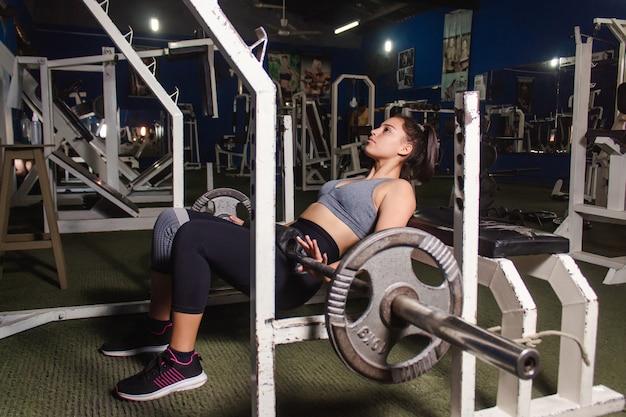 Junges fitnessmädchen, das gluteusübung mit langhantel im fitnessstudio macht.