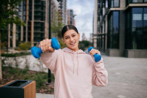 Junges fitnessmädchen, das übungen mit hanteln im stadtpark macht