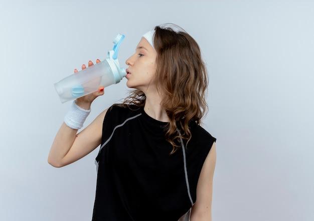 Junges fitnessmädchen im schwarzen sportbekleidungs-trinkwasser nach dem training, das über weißer wand steht