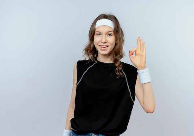 Junges fitnessmädchen in der schwarzen sportbekleidung mit dem lächelnden stirnband, das okes zeichen steht über weißer wand zeigt