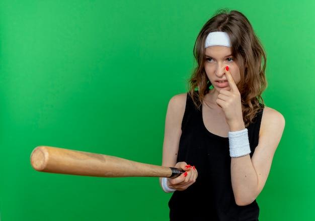 Junges fitnessmädchen in der schwarzen sportbekleidung mit dem stirnband, das basaball fledermaus hält, der jemanden betrachtet, der sie beobachtet, wie sie geste zeigen, die mit dem finger auf ihr auge zeigt, das über grüner wand steht