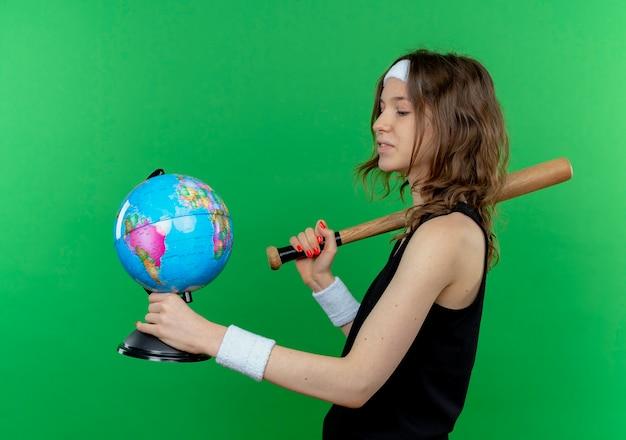 Junges fitnessmädchen in der schwarzen sportbekleidung mit dem stirnband, das baseballschläger und globus hält, der es mit ernstem gesicht betrachtet, das über grüner wand steht