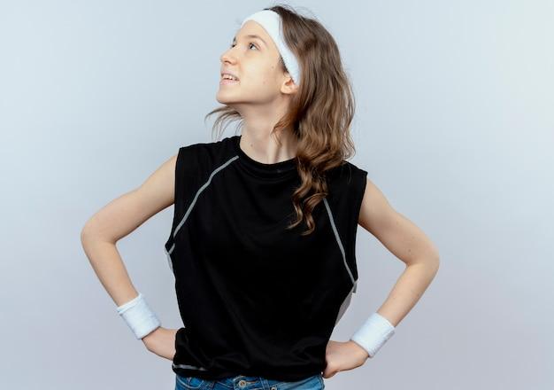 Junges fitnessmädchen in der schwarzen sportbekleidung mit dem stirnband, das beiseite mit lächeln auf gesicht mit armen an der hüfte steht, die über weißer wand steht
