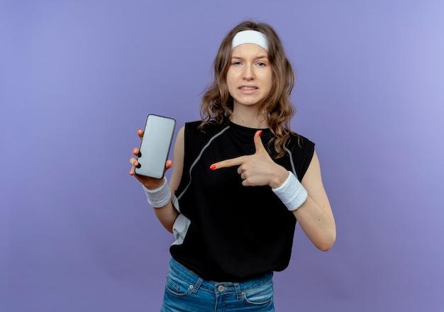 Junges fitnessmädchen in der schwarzen sportbekleidung mit dem stirnband, das das smartphone zeigt, das mit dem zeigefinger darauf schaut und zuversichtlich steht, über der blauen wand zu stehen