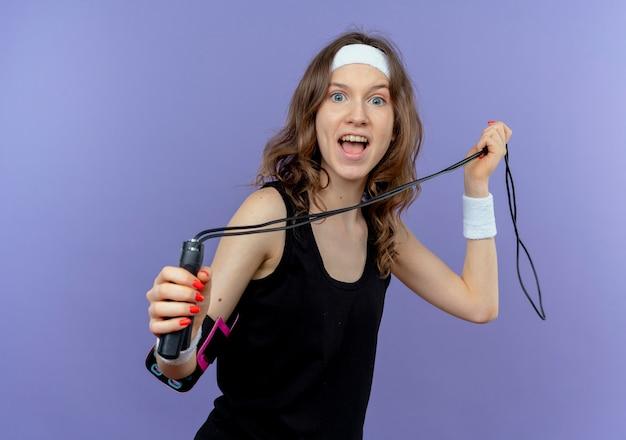 Junges fitnessmädchen in der schwarzen sportbekleidung mit dem stirnband, das das springseil glücklich und aufgeregt über der blauen wand hält