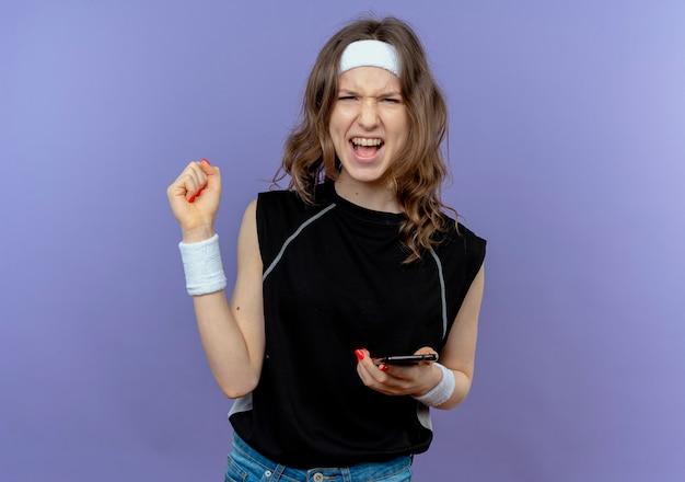 Junges fitnessmädchen in der schwarzen sportbekleidung mit dem stirnband, das die glückliche und aufgeregte faust des smartphones hält, die über der blauen wand steht