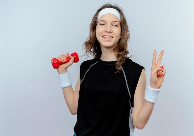 Junges fitnessmädchen in der schwarzen sportbekleidung mit dem stirnband, das die lächelnde hantel hält, die siegeszeichen zeigt, das über weißer wand steht