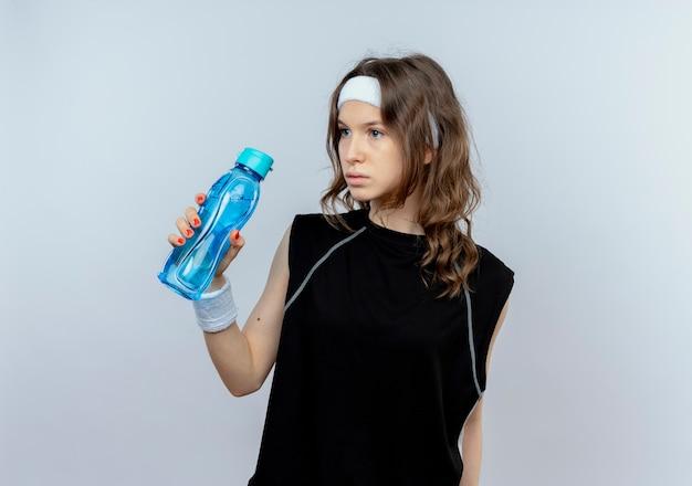 Junges fitnessmädchen in der schwarzen sportbekleidung mit dem stirnband, das flasche wasser hält, das beiseite steht, verwirrt über weißer wand steht