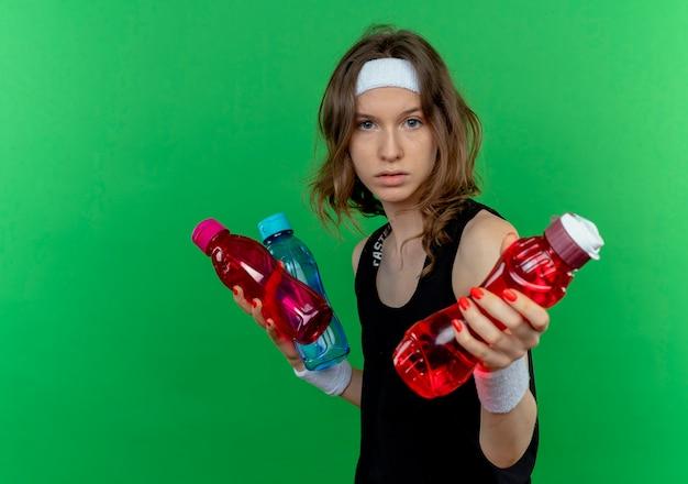 Junges fitnessmädchen in der schwarzen sportbekleidung mit dem stirnband, das flaschen des wassers hält, das eine der flaschen anbietet, die über grüner wand stehen