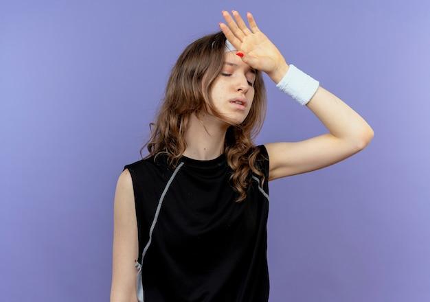 Junges fitnessmädchen in der schwarzen sportbekleidung mit dem stirnband, das mit der hand auf ihrem kopf für fehler über blau verwirrt schaut