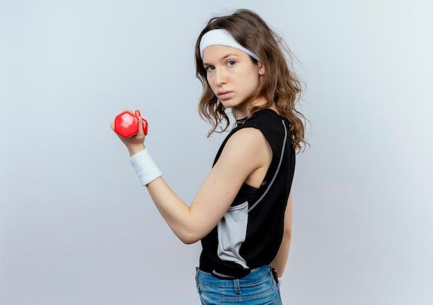 Junges fitnessmädchen in der schwarzen sportbekleidung mit dem stirnband, das mit der hantel arbeitet, die zuversichtlich steht, über weißer wand zu stehen