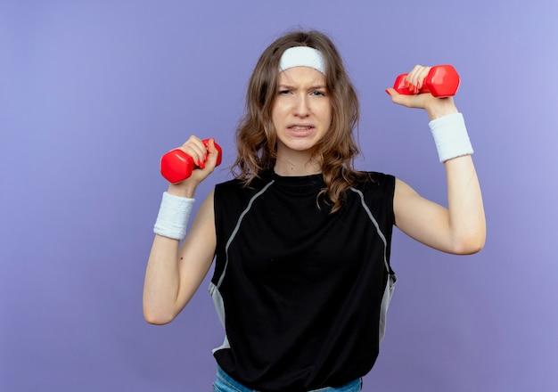 Junges fitnessmädchen in der schwarzen sportbekleidung mit dem stirnband, das mit kurzhanteln arbeitet, die verwirrt stehen über blauer wand stehen