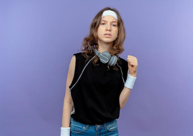 Junges fitnessmädchen in der schwarzen sportbekleidung mit dem stirnband, das selbstbewusste geballte faust steht, die über blaue wand steht