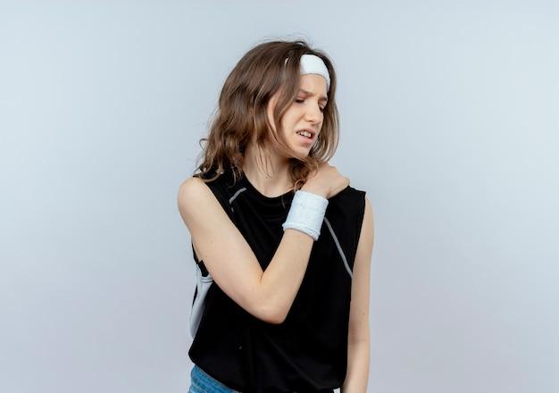 Junges fitnessmädchen in der schwarzen sportbekleidung mit dem stirnband, das unwohl schaut, das ihre schulter berührt, die schmerzen hat, die über weißer wand stehen