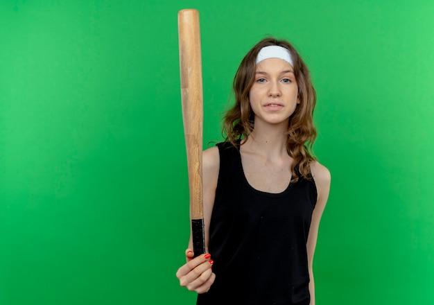 Junges fitnessmädchen in der schwarzen sportbekleidung mit dem stirnband, der basaball fledermaus mit dem sicheren ausdruck steht, der über grüner wand steht