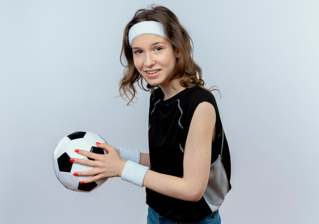 Junges fitnessmädchen in der schwarzen sportbekleidung mit dem stirnband, der fußball lächelnd steht, der über weißer wand steht