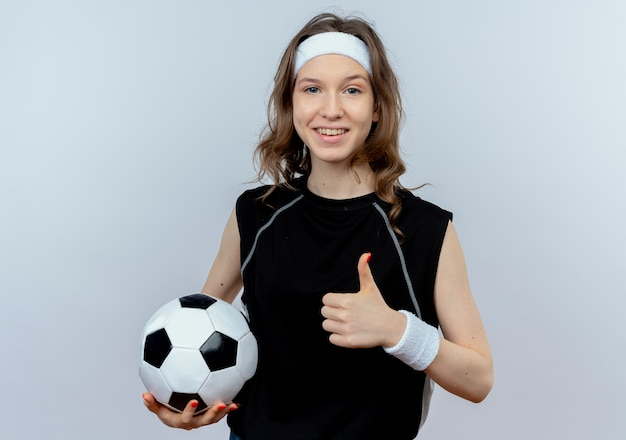 Junges fitnessmädchen in der schwarzen sportbekleidung mit dem stirnband, der fußball lächelnd zeigt, zeigt daumen hoch, die über weißer wand stehen