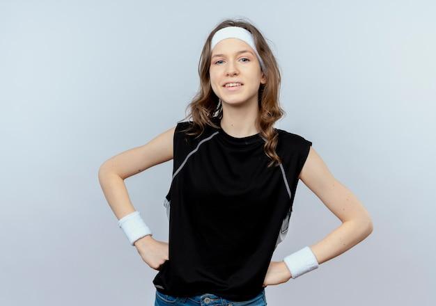 Junges fitnessmädchen in der schwarzen sportbekleidung mit dem stirnband, der zuversichtlich mit den armen an der hüfte lächelt, die über weißer wand stehen