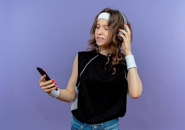 Junges fitnessmädchen in der schwarzen sportbekleidung mit dem stirnband und den kopfhörern, die ihr smartphone suchen musik suchen, die über blaue wand steht