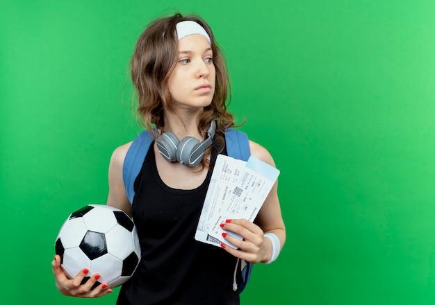 Junges fitnessmädchen in der schwarzen sportbekleidung mit rucksack und stirnband, die fußball und flugtickets halten, die beiseite stehen, verwirrt über grüner wand stehen
