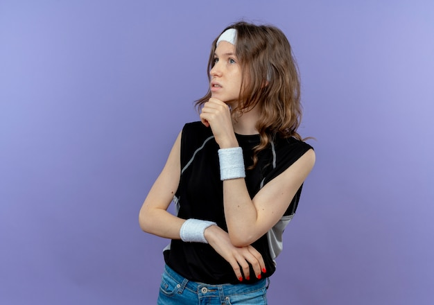 Junges fitnessmädchen in der schwarzen sportbekleidung mit stirnband, das mit hand auf kinn beiseite schaut, verwirrt mit nachdenklichem ausdruck auf gesicht, das über blauer wand steht
