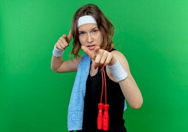 Junges fitnessmädchen in der schwarzen sportbekleidung mit stirnband und handtuch auf der schulter, die mit den fingern zeigt, die über grüner wand sicher stehen