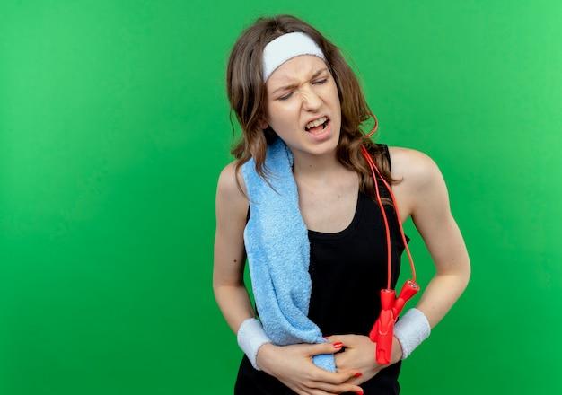 Junges fitnessmädchen in der schwarzen sportbekleidung mit stirnband und handtuch auf der schulter, die unwohl berührt, ihren bauch fühlend, der schmerz fühlt, der über grüner wand steht