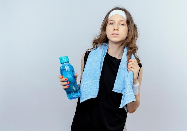 Junges fitnessmädchen in der schwarzen sportbekleidung mit stirnband und handtuch um den hals, die flasche wasser mit ernstem gesicht hält, das über weißer wand steht
