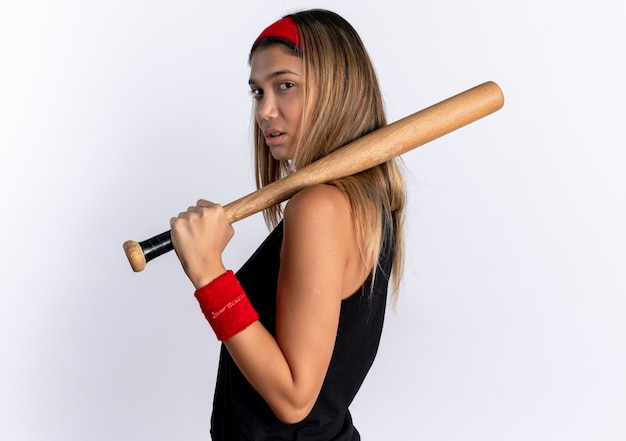 Junges fitnessmädchen in der schwarzen sportbekleidung und im roten stirnband, die baseballschläger halten, der zuversichtlich steht, über weißer wand steht
