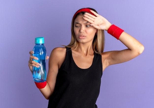 Junges fitnessmädchen in der schwarzen sportbekleidung und im roten stirnband, die flasche wasser halten, das müde und erschöpft nach dem training steht, das über der blauen wand steht