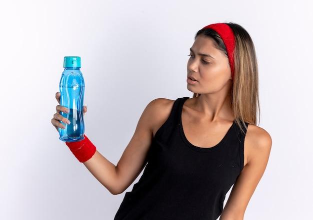 Junges fitnessmädchen in der schwarzen sportbekleidung und im roten stirnband, die flasche wasser halten, die es mit verwirrendem ausdruck betrachtet, der über weißer wand steht