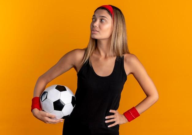 Junges fitnessmädchen in der schwarzen sportbekleidung und im roten stirnband, die fußball halten, der beiseite mit dem sicheren ausdruck über orange schaut
