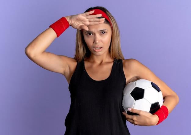 Junges fitnessmädchen in der schwarzen sportbekleidung und im roten stirnband, die fußball halten, der weit weg mit hand über kopf über blau schaut