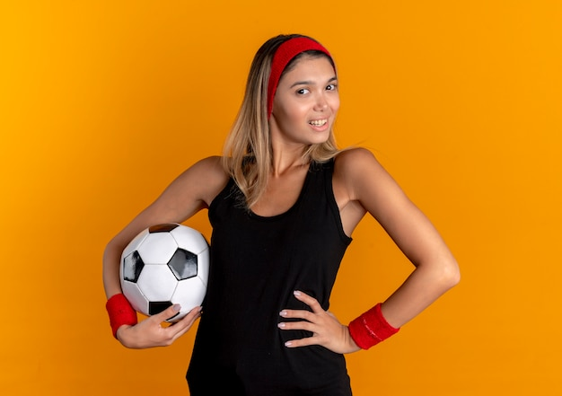 Junges fitnessmädchen in der schwarzen sportbekleidung und im roten stirnband, die fußball halten, der zuversichtlich mit lächeln steht, das über orange wand steht